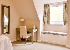 Window seat and writing table in a bedroom at Dalmunzie house